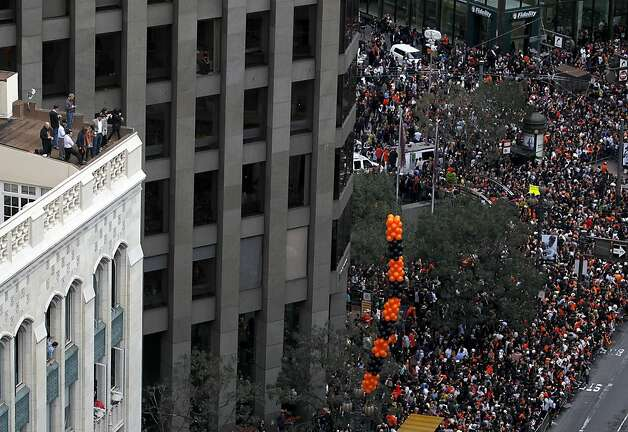 Office workers are perched high above thousands of fans below for the Giants' World Series victory parade from a building on Market Street in San Francisco, Calif. on Wednesday, Oct. 31, 2012. Photo: Paul Chinn, The Chronicle