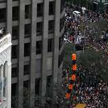 Office workers are perched high above thousands of fans below for the Giants' World Series victory parade from a building on Market Street in San Francisco, Calif. on Wednesday, Oct. 31, 2012.
