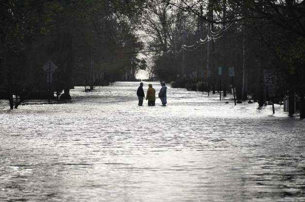 Rowland Road on Tuesday morning more resembled a river, where three men waded in to meet. Photo: Contributed Photo, Matthew Jamison/Contributed Phot