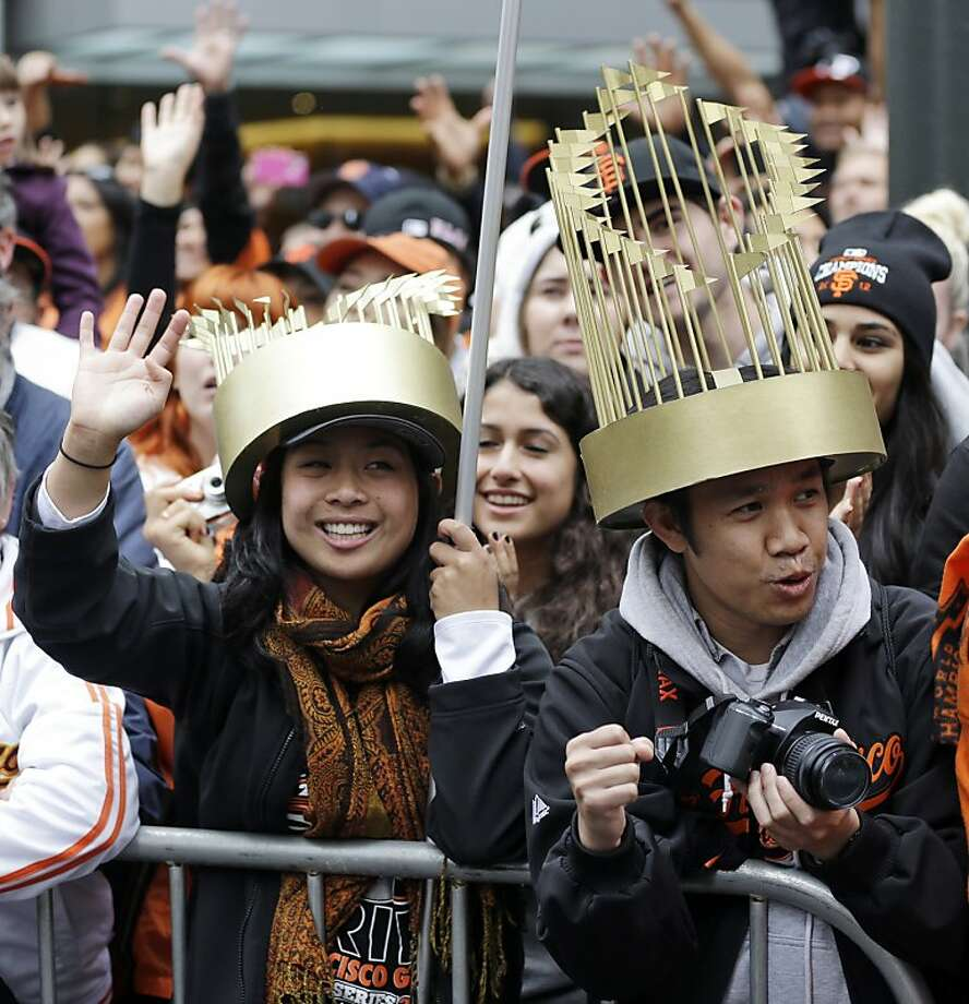 Fans Elizabeth Santos, left and Joseph Foranda wear World Series trophy hats during the San Francisco Giants' baseball World Series victory parade, Wednesday, Oct. 31, 2012, in San Francisco.(AP Photo/Sanchez) Photo: Sanchez, Associated Press