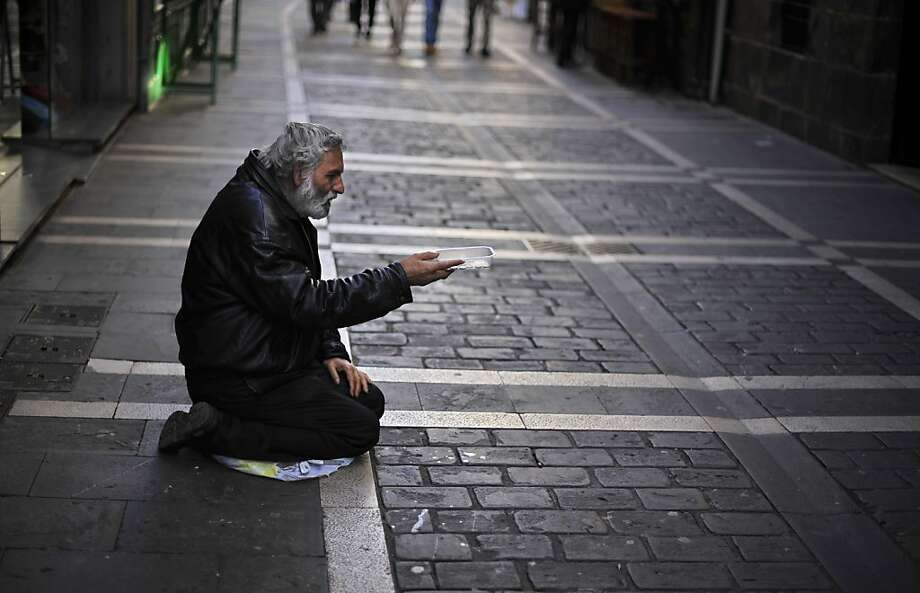 On his knees: A down-and-out Spaniard begs for alms in a street in Pamplona. The country is struggling with 25-percent unemployment. Photo: Alvaro Barrientos, Associated Press