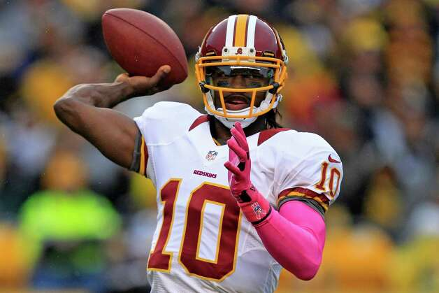 "FILE - In this Oct. 28, 2012 file photo, Washington Redskins football quarterback Robert Griffin III throws pass in the first quarter of an  NFL football game against the Pittsburgh Steelers in Pittsburgh. In a rare show of unity, President Barack Obama and challenger Mitt Romney took turns praising Griffin a couple of weeks ago for a video that aired on the Fox network NFL pregame show. They uttered polished, rote lines such as Romney's ""RG3 hasn't been in Washington very long, but he's already created change"" and Obama's ""You're welcome at my house for a pickup game anytime.""  (AP Photo/Gene J. Puskar, File) Photo: Gene J. Puskar, Associated Press / AP"