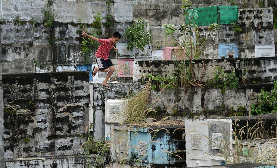 "Tomb hopper:A boy jumps from one ""apartment"" grave to another at a cemetery in Manila. Millions of Filipinos will flock to cemeteries on Nov. 1 and 2, offering flowers, candles and prayers to departed loved ones in a traditional commemoration of the dead. Photo: Noel Celis, AFP/Getty Images"