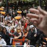 Diane Schultz, 65, with guest services, throws chocolate form a Ride the Ducks vehicle to fans along the parade route during the San Francisco Giants World Series victory parade on Wednesday, October 31, 2012 in San Francisco, Calif.