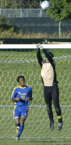 Lanky Spartan goalkeeper Kellen Rikhoff rises high above a Yellowjacket scoring hopeful to bat away a rival corner kick during the Shepaug Valley High School boys' soccer match vs. Gilbert, Oct. 11, 2012 in Washington. Photo: Norm Cummings