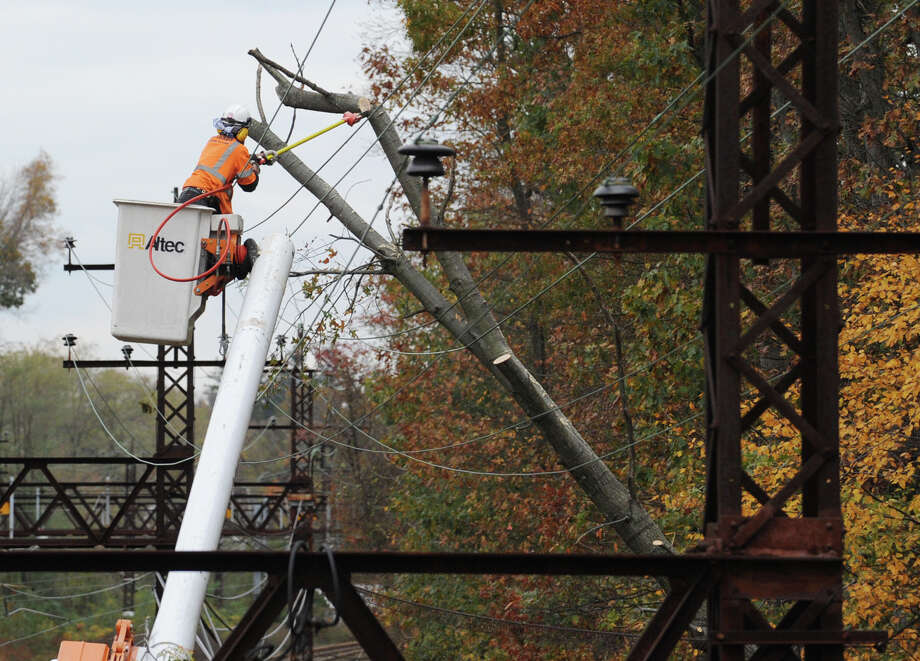 A Metro-North clean-up crew attempts to clear a downed tree that was resting on the electric lines by the railroad tracks near the West Street overpass in Mamaroneck, N.Y., Wednesday  Oct. 31, 2012, during the aftermath of Hurricane Sandy. Photo: Bob Luckey / Greenwich Time
