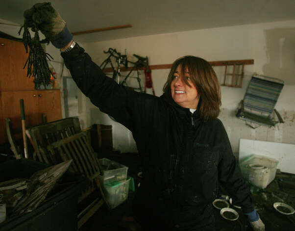 Marsha Magun picks up a clump of seaweed as she cleans her garage filled with mud from the floodwaters of Hurricane Sandy on Point Beach Drive in Milford on Wednesday, October 31, 2012. Photo: Brian A. Pounds, Connecticut Post / Connecticut Post