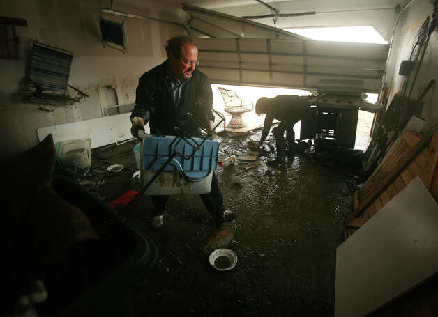 Terry and Marsha Magun work to clean their garage filled with mud from the floodwaters of Hurricane Sandy on Point Beach Drive in Milford on Wednesday, October 31, 2012. Photo: Brian A. Pounds, Connecticut Post / Connecticut Post