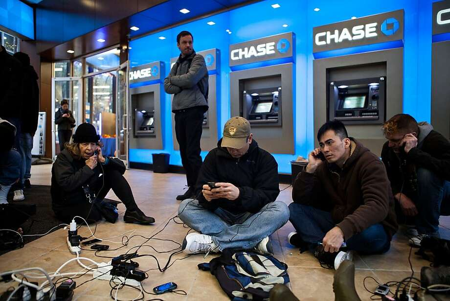 "People crowd into a Chase Bank ATM kiosk to charge phones and laptops at 40th Street and 3rd Avenue, one block north of where power has gone out, on October 31, 2012 in New York, United States. ""This is the modern campfire,"" one man mentioned to another man. Businesses across the eastern seaboard are attempting to return to normal operations as clean-up from Hurricane Sandy continues.  (Photo by Andrew Burton/Getty Images) Photo: Andrew Burton, Getty Images"