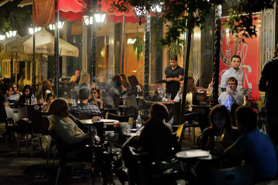 Egyptians relax in Cairo on Wednesday. Egypt's capital prides itself on being a city that never sleeps, but officials have ordered most businesses to close early. Photo: STF / AP