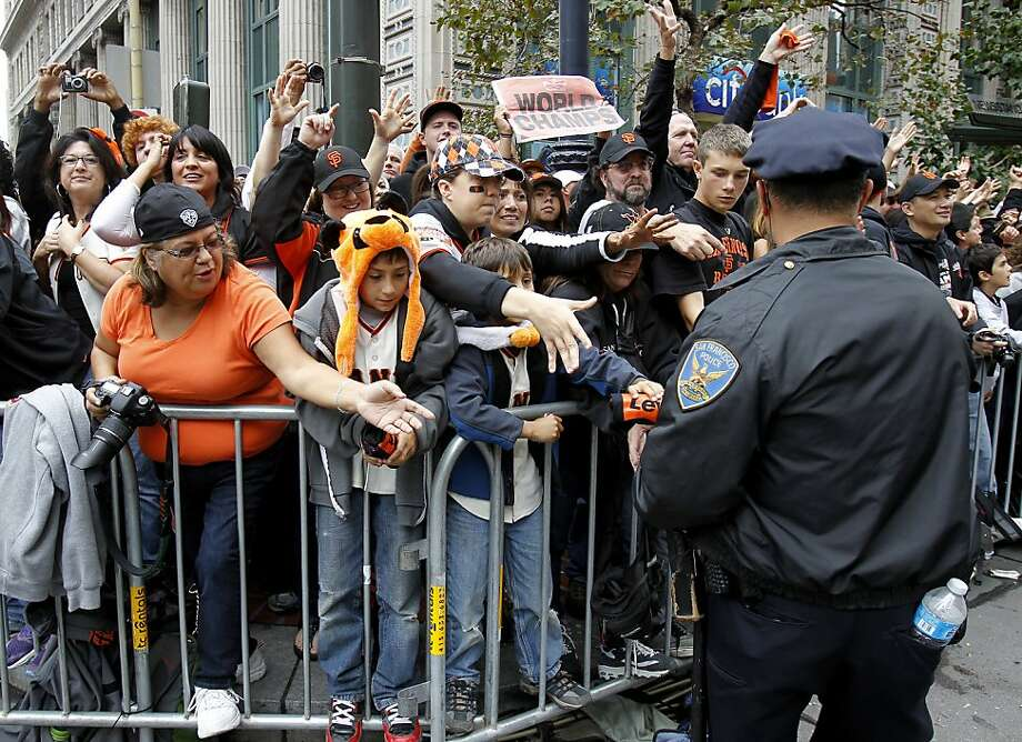 San Francisco police officer Jeff Aloise retrieved candy for fans along Market Street. The San Francisco Giants celebrated their second World Series title in three years with a parade down Market Street Wednesday October 31, 2012. Photo: Brant Ward, The Chronicle