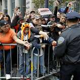 San Francisco police officer Jeff Aloise retrieved candy for fans along Market Street. The San Francisco Giants celebrated their second World Series title in three years with a parade down Market Street Wednesday October 31, 2012.
