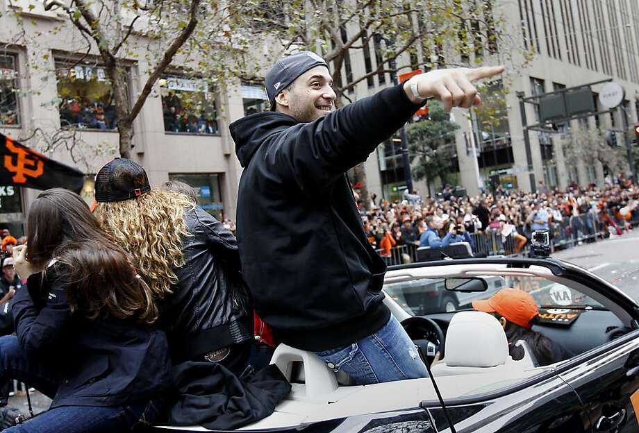 Marco Scutaro pointed to the crowd with a big grin as he made his way down Market Street. The San Francisco Giants celebrated their second World Series title in three years with a parade down Market Street Wednesday October 31, 2012. Photo: Brant Ward, The Chronicle