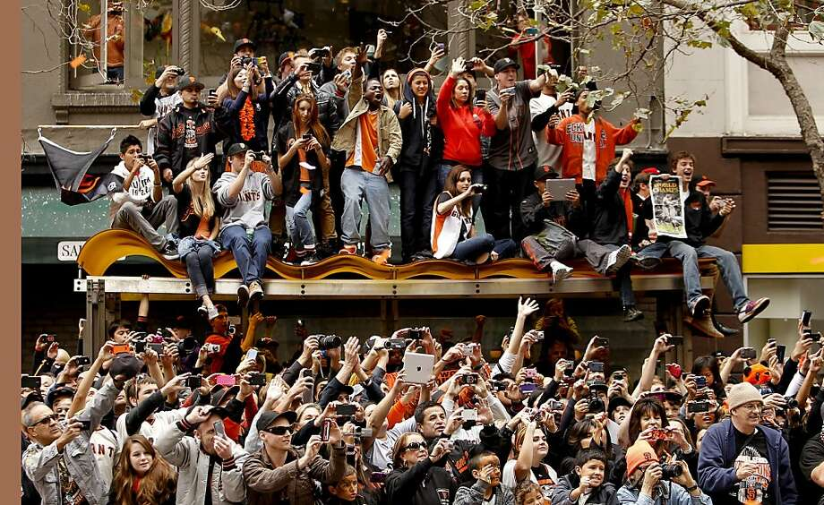 Fans filled the sidewalks and struggled as best they could to see their heroes on the Giants - and take lots of pictures - during the victory parade. Photo: Michael Macor, The Chronicle