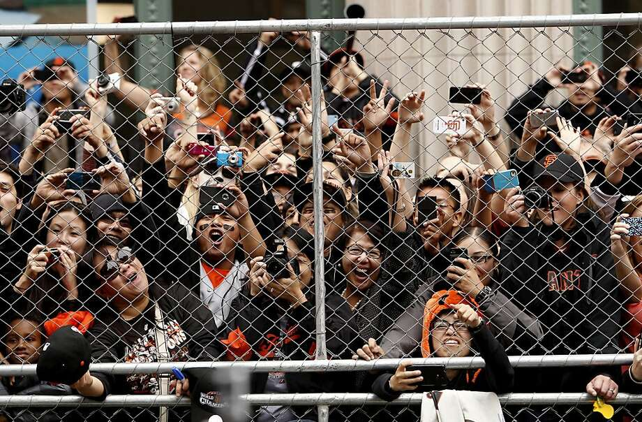 Fans don't let a chain link fence bother them as they get a glimpse of their favorite play as the San Francisco Giants celebrate their World Series Championship with a parade up Market Street in downtown San Francisco, Calif., on Wednesday Oct. 31, 2012. Photo: Michael Macor, The Chronicle
