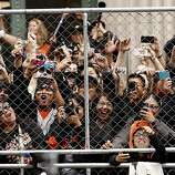Fans don't let a chain link fence bother them as they get a glimpse of their favorite play as the San Francisco Giants celebrate their World Series Championship with a parade up Market Street in downtown San Francisco, Calif., on Wednesday Oct. 31, 2012.