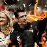 San Francisco Giants' Buster Posey and his wife Kristen wave to fans as the San Francisco Giants celebrate their World Series Championship with a parade up Market Street in downtown San Francisco, Calif., on Wednesday Oct. 31, 2012.