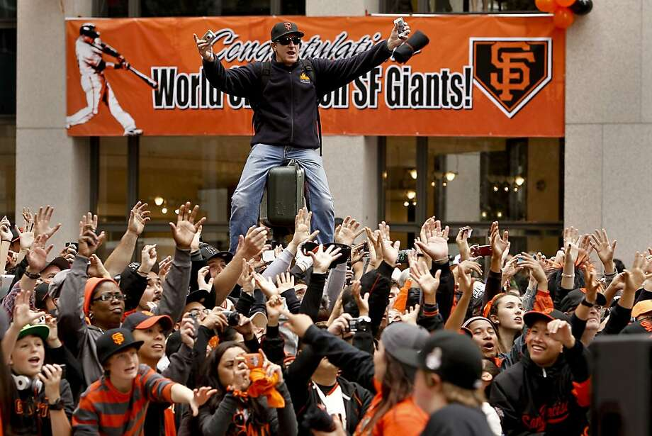 A fan climbed a street lights for a better view as the San Francisco Giants celebrated their World Series Championship with a parade up Market Street in downtown San Francisco, Calif., on Wednesday Oct. 31, 2012. Photo: Michael Macor, The Chronicle