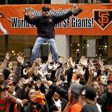 A fan climbed a street lights for a better view as the San Francisco Giants celebrated their World Series Championship with a parade up Market Street in downtown San Francisco, Calif., on Wednesday Oct. 31, 2012.