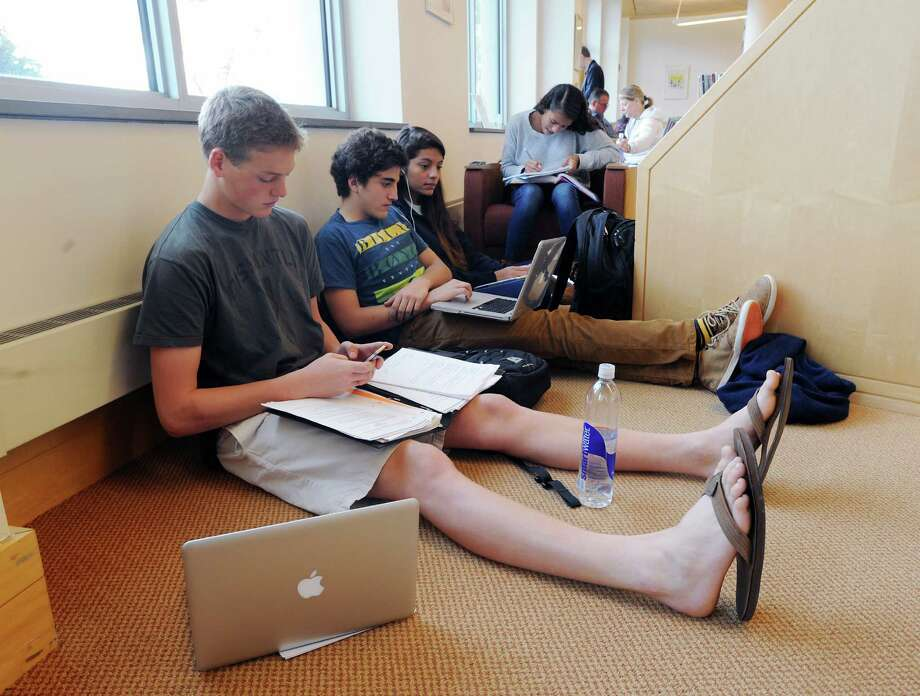 At left, Kurt Vogt, 16, of Greenwich and friends connected to the internet at Greenwich Library, Wednesday morning, Oct. 31, 2012.  Vogt said there was no school due to Hurricane Sandy and that his home is without electricity so he decided the library and its amenities was the ideal place to go. Photo: Bob Luckey, Connecticut Post / Greenwich Time