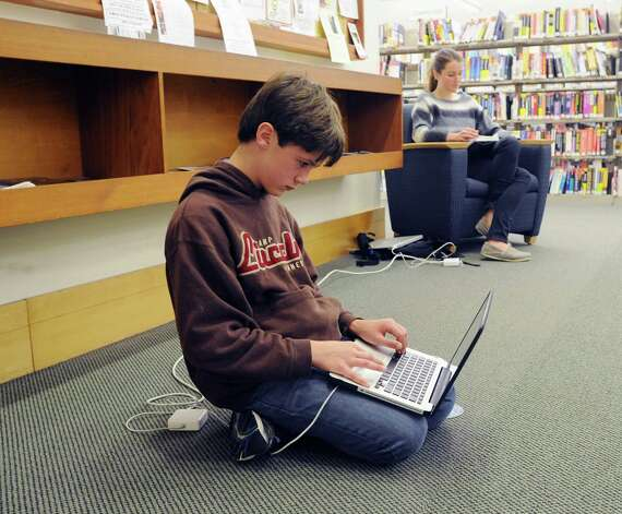 Wiliam Dunn, 12, of Greenwich, plugged in and using the internet at Greenwich Library, Wednesday morning, Oct. 31, 2012. Dunn and much of Greenwich are still without electricity due to Hurricane Sandy making the  library and its amenities have become a gathering spot for the community. Photo: Bob Luckey, Connecticut Post / Greenwich Time