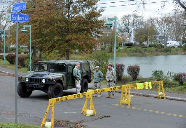 Members of the National Guard stand at the intersection of Sailors Lane and Gilman Street near Saint Mary's By the Sea Wednesday, Oct. 31, 2012 in Bridgeport, Conn.  Access to the Saint Mary's By the Sea area of Bridgeport was limited to residents following Hurricane Sandy. Photo: Autumn Driscoll, Connecticut Post / Connecticut Post