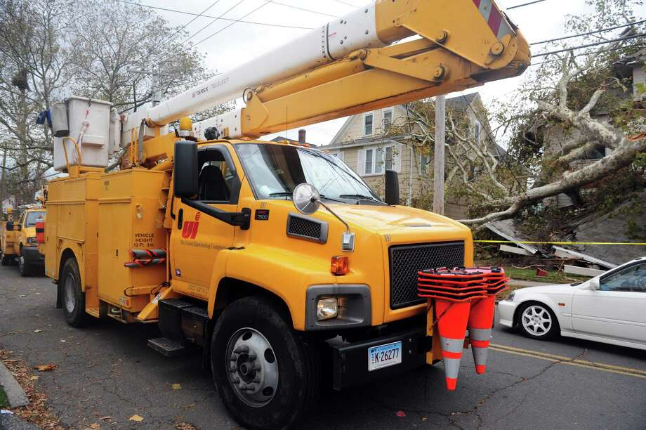 A United Illuminating truck drives down Grovers Avenue Wednesday, Oct. 31, 2012 in Bridgeport, Conn. Drivers told neighbors that they would be back to address the downed power lines on Grovers Avenue in two days. Photo: Autumn Driscoll, Connecticut Post / Connecticut Post