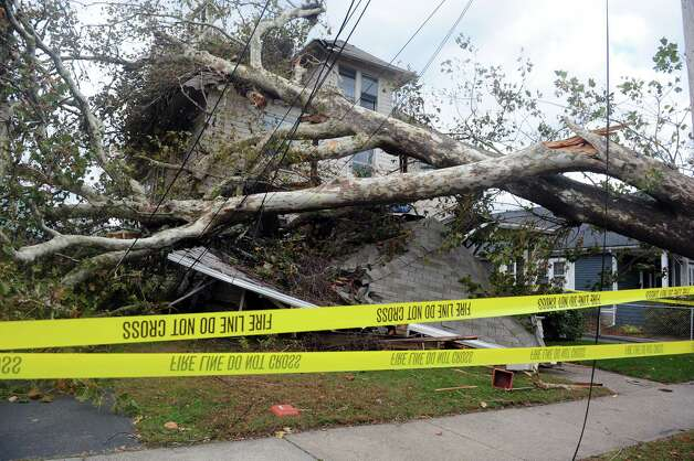 A house on Grovers Avenue is destroyed by a fallen tree from Hurricane Sandy Wednesday, Oct. 31, 2012 in Bridgeport, Conn. Photo: Autumn Driscoll, Connecticut Post / Connecticut Post
