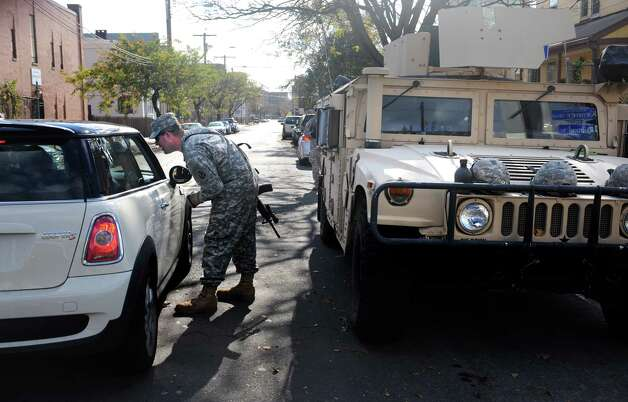 A member of the National Guard checks identification at the intersection of Lafayette Street and Railroad Avenue Wednesday, Oct. 31, 2012 in Bridgeport, Conn.  Access to the Seaside Park area of Bridgeport was limited to residents following Hurricane Sandy. Photo: Autumn Driscoll, Connecticut Post / Connecticut Post