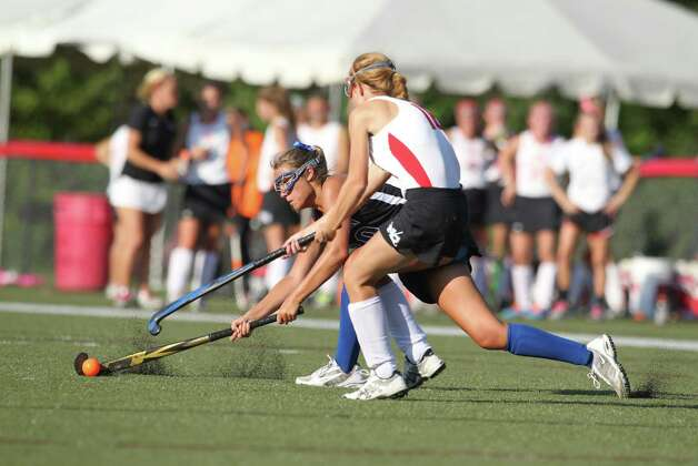 Darien field hockey player Jackie Brokaw drives the ball upfield despite the defensive efforts of New Canaan defender Abby Jameson in seond half action in New Canaan, Conn. on Wednesday, Sept. 12, 2012. Photo: J. Gregory Raymond