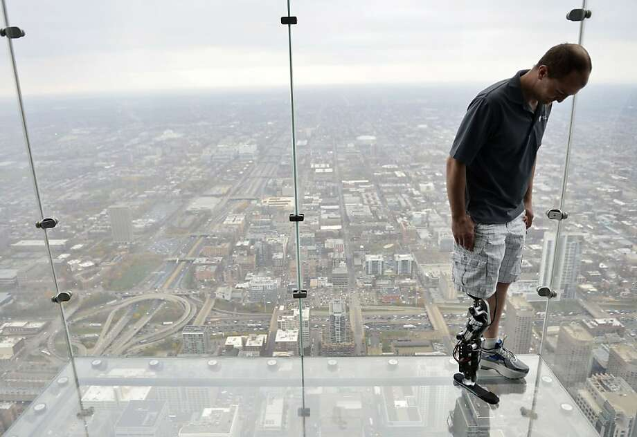 Zac Vawter, fitted with an experimental bionic leg, looks down from the ledge on the Willis Tower in Chicago, where he'll try to climb 103 flights using the new prosthesis. Photo: Brian Kersey, Associated Press