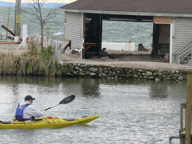 A man kayaks down Pine Creek Wednesday past damaged homes on Fairfield Beach Road. Photo: Genevieve Reilly