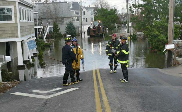 Emergency crews assess damaged homes on Fairfield Beach Road, checking for occupants and structural damage. Photo: Genevieve Reilly
