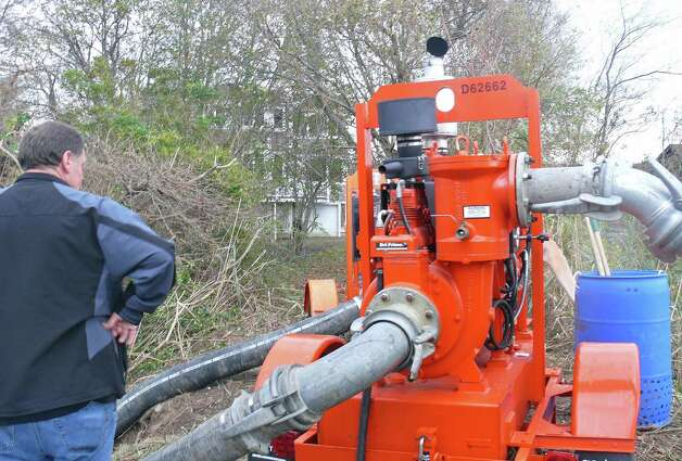 "Public Works Supt. Scott Bartlett checks out a ""monster pump"" that was being used to try and lower the water level in beach neighborhoods Wednesday. Photo: Genevieve Reilly"