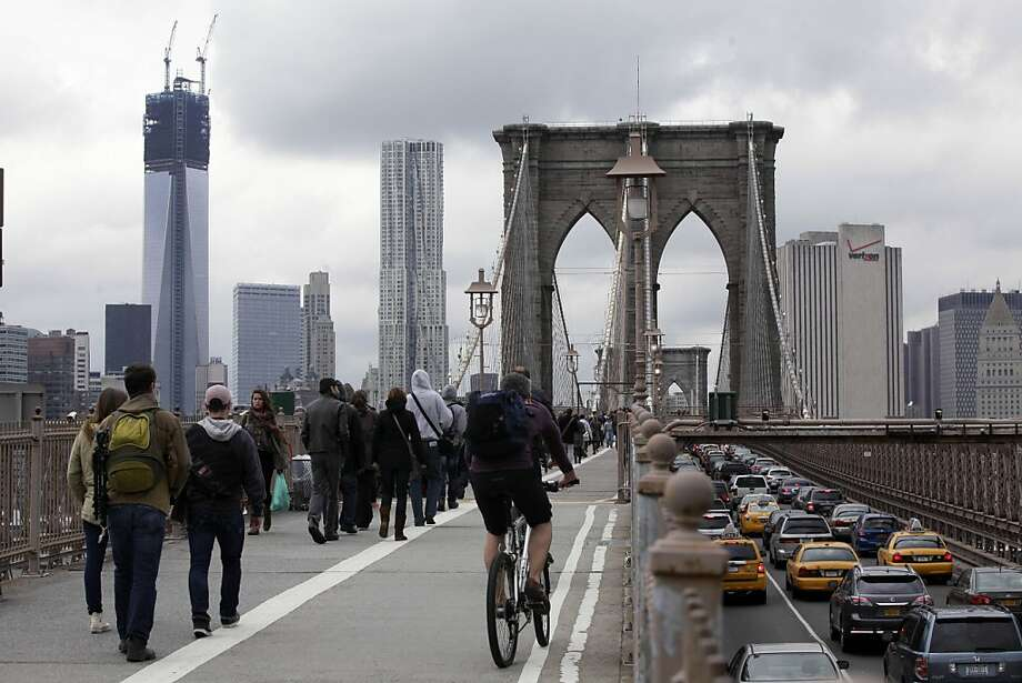Commuters cross New York's Brooklyn Bridge, Wednesday, Oct. 31, 2012. The floodwaters that poured into New York's deepest subway tunnels may pose the biggest obstacle to the city's recovery from the worst natural disaster in the transit system's 108-year history.  (AP Photo/Richard Drew) Photo: Richard Drew, Associated Press
