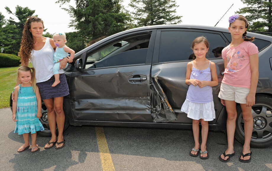 Samara Ceccucci stands with her daughters, from left, Noli, 3, Eleanor, 11 mos., Adison,  7, and Mia, 10, in front of the family's damaged Toyota Prius. The car was hit by a Troy police cruiser, but the city has so far declined to pay the damages. (Lori Van Buren / Times Union)