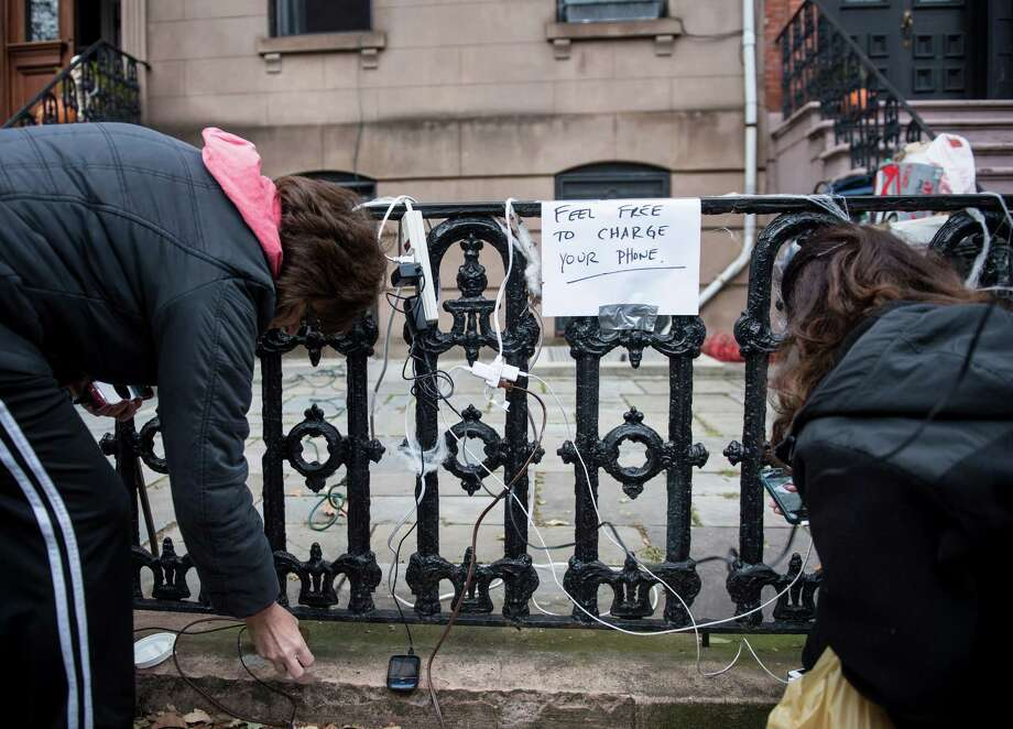 A fortunate resident who still has electricity sets up a free cellphone charging station Wednesday in Hoboken, N.J., to help neighbors left in the dark. Photo: BRENDAN SMIALOWSKI, Staff / AFP