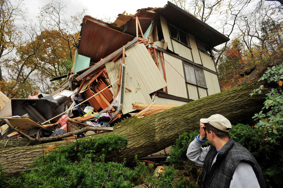 Reynaldo Lopez surveys the damage to his family's home in Danbury on Wednesday, Oct. 31, 2012. The house sustained the damage due to a large tree falling on it Monday evening because of storm Sandy. The family was inside their home when it was hit, but nobody was hurt. Photo: Jason Rearick