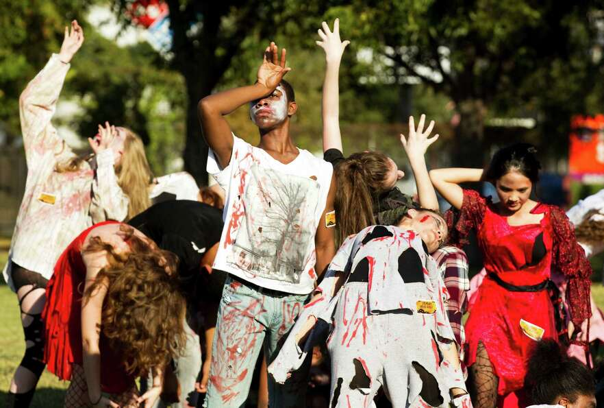 A group of high school students dressed as zombies perform a dance  outside the polling place at the