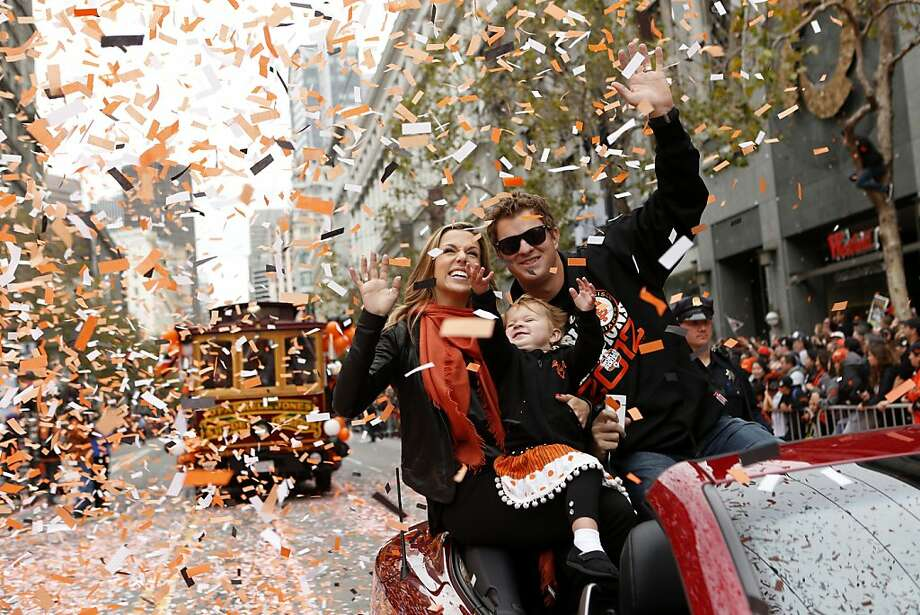 Giants pitcher Matt Cain, wife Chelsea and daughter Hartley wave during the World Series victory parade on Market Street. Photo: Beck Diefenbach, Special To The Chronicle