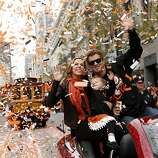Giants pitcher Matt Cain, wife Chelsea and daughter Hartley wave during the World Series victory parade on Market Street.