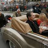 Officials push the Rolls-Royce carrying Giants manager Bruce Bochy, which had run out of gas. Bochy is holding the Giants' World Series trophy.