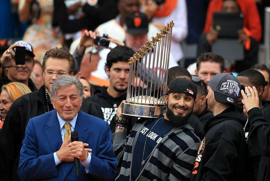 "Singer Tony Bennett performs ""I Left My Heart in San Francisco"" as Giants relief pitcher Sergio Romo shows the World Series trophy to the crowd outside City Hall. Photo: Lacy Atkins, The Chronicle"