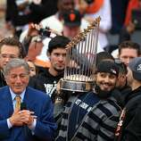"Singer Tony Bennett performs ""I Left My Heart in San Francisco"" as Giants relief pitcher Sergio Romo shows the World Series trophy to the crowd outside City Hall."