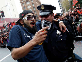 Sergio Romo and a San Francisco police officer in happier times, at the Giants' World Series victory parade in 2012.