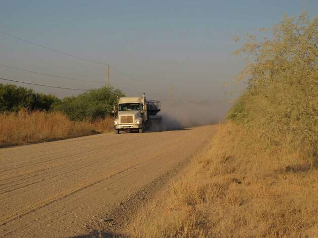 A truck travels along the stretch of gravel road near La Joya, Texas, Friday Oct. 26, 2012, where a Texas Department of Public Safety helicopter and sharpshooter assisted the previous day in the chase of a suspected illegal immigrant smuggler. Two people in the fleeing vehicle were killed and a third was wounded. (AP Photo/Chris Sherman) Photo: Chris Sherman, Associated Press / AP