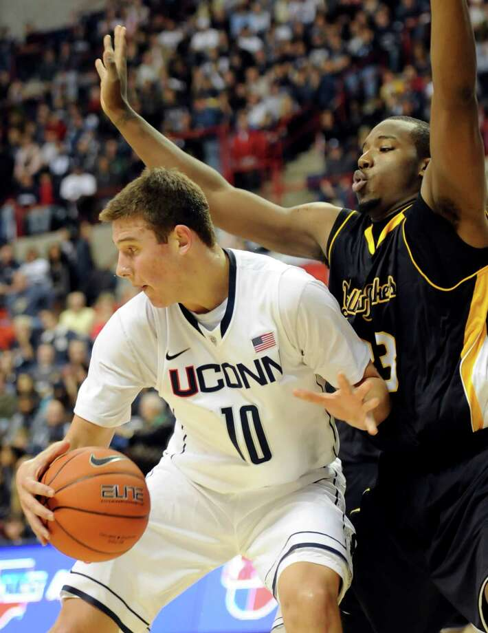 Connecticut's Tyler Olander, left, is defended by American International's Braxton Gardner in the first half of an NCAA college exhibition basketball game Wednesday, Nov. 2, 2011, in Storrs, Conn. (AP Photo/Bob Child) Photo: Bob Child, Associated Press / FRE 170410 AP