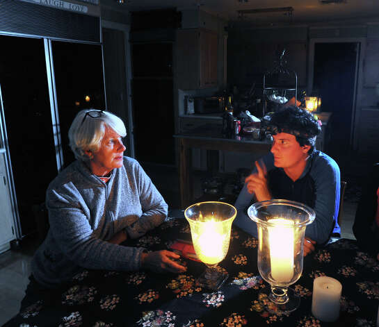 Sitting at her Kitchen table by candle light, Old Greenwich resident Karen Sadik-Khan, left, discusses with her son, Altan, the devastation wrought by Hurricane Sandy to their Binney Lane neighborhood, Wednesday night, Oct. 31, 2012. Photo: Bob Luckey / Greenwich Time