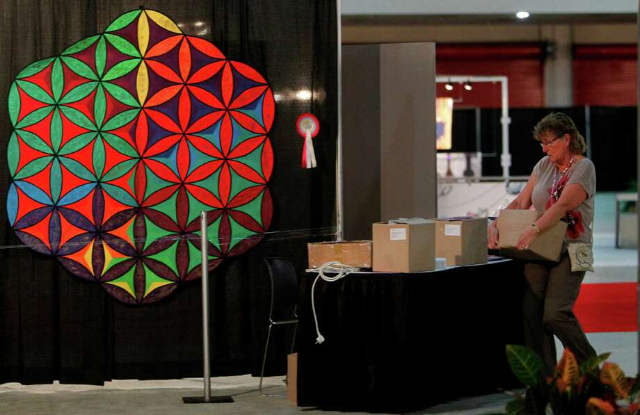 Ada Honders, of Open European Quilt Champions, quickly sets up her booth as staff prepares to open doors tonight to the International Quilt Festival at the George R. Brown Convention Center on Wednesday, Oct. 31, 2012, in Houston. Photo: Mayra Beltran, Houston Chronicle / © 2012 Houston Chronicle