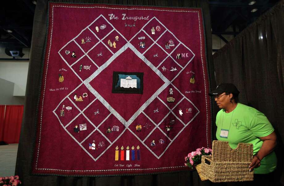 Pamela Tilley, of Texas Women Veterans, sets up her information table after hanging the quilt designed by veterans to be on display during the International Quilt Festival at the George R. Brown Convention Center on Wednesday, Oct. 31, 2012, in Houston. Photo: Mayra Beltran, Houston Chronicle / © 2012 Houston Chronicle